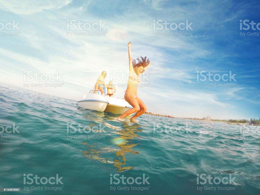 Tres mujeres jóvenes pedal barco - buceo en el agua - foto de stock