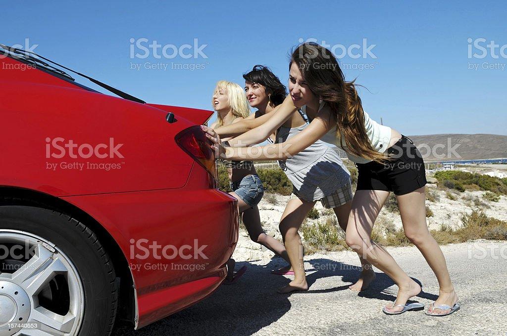 Three Young Women Pushing Red Car Along Road stock photo
