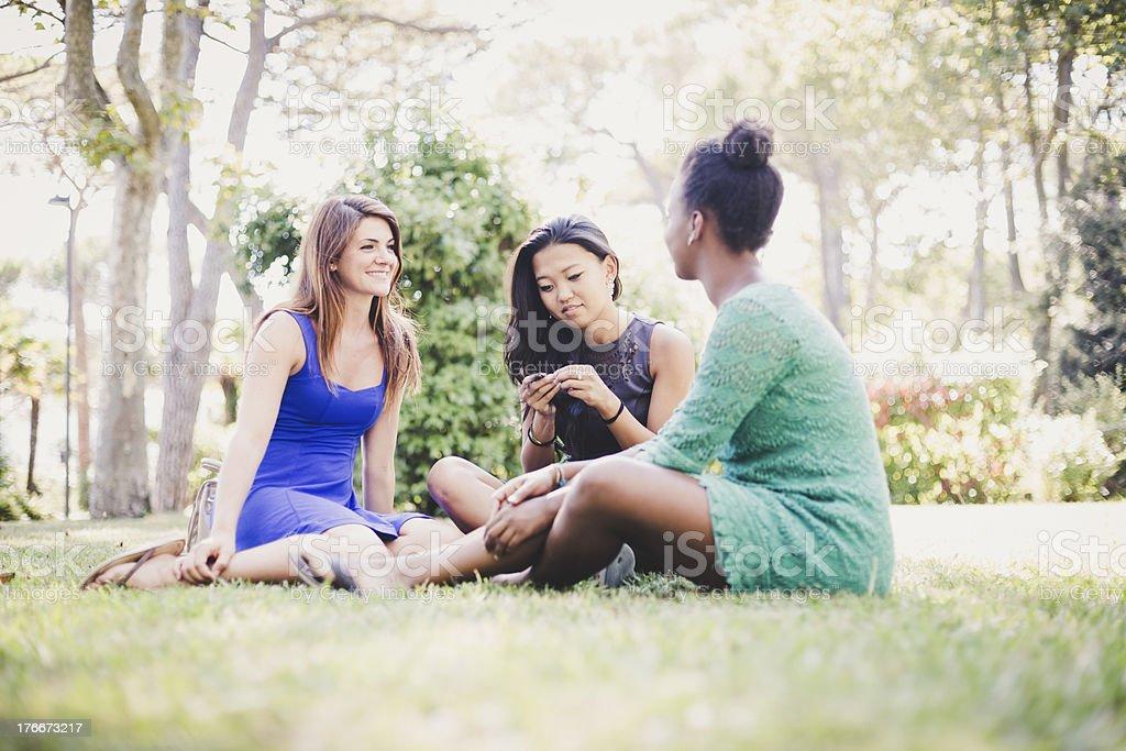 Tres mujeres jóvenes relajante en el parque foto de stock libre de derechos