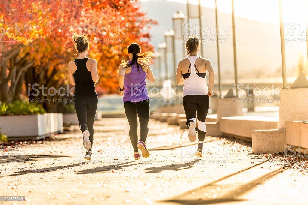 three young women running stock photo