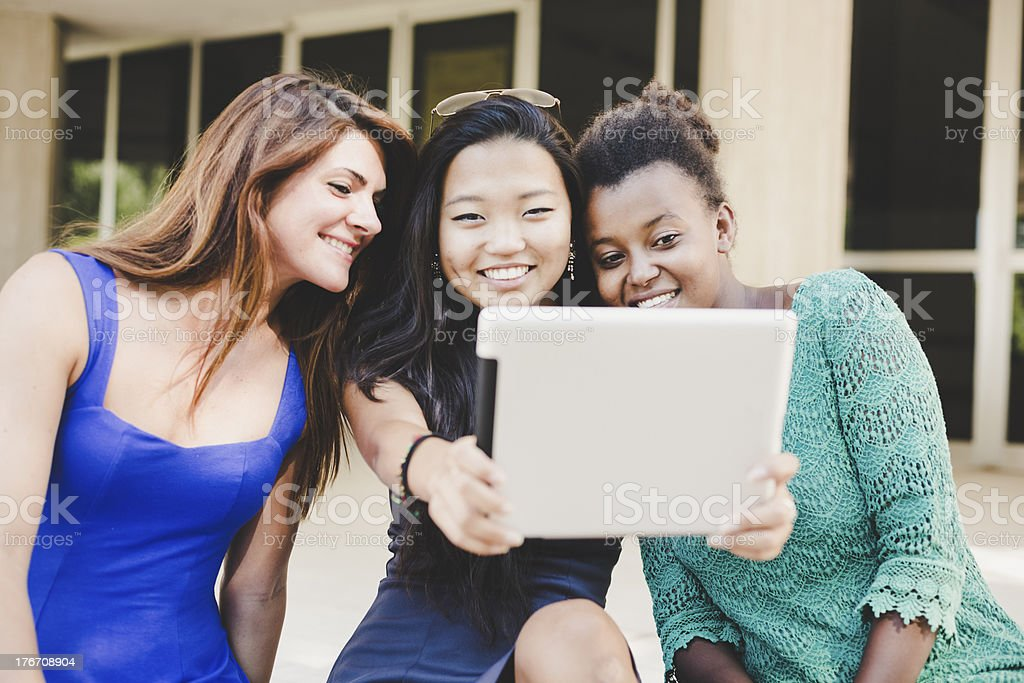 Three young women taking self portrait with digital tablet royalty-free stock photo