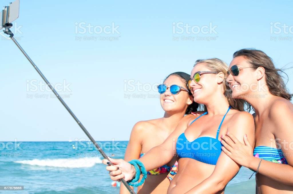Three young women taking selfie by the sea royalty-free stock photo