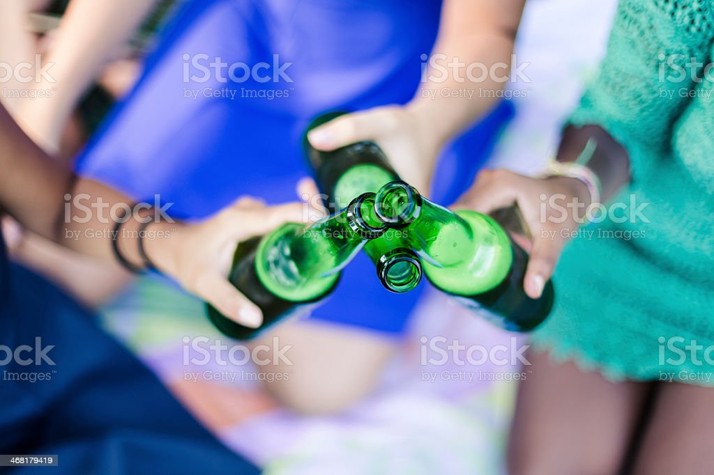 Three young women toasting while drinking beers royalty-free stock photo