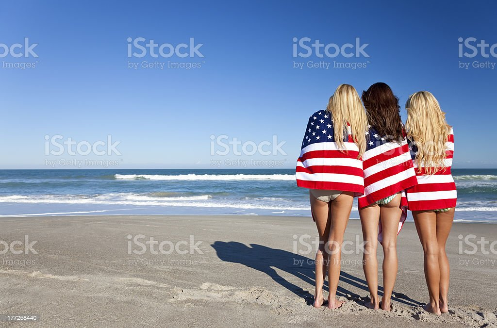Three Young Women Wrapped in American Flags on a Beach stock photo