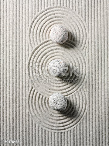 Three zen stones and circles in sand. Overhead view