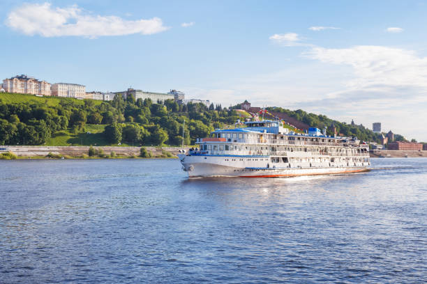 Cтоковое фото Three-deck river boat in the rays of the evening sun goes along the banks of the Volga near Nizhny Novgorod