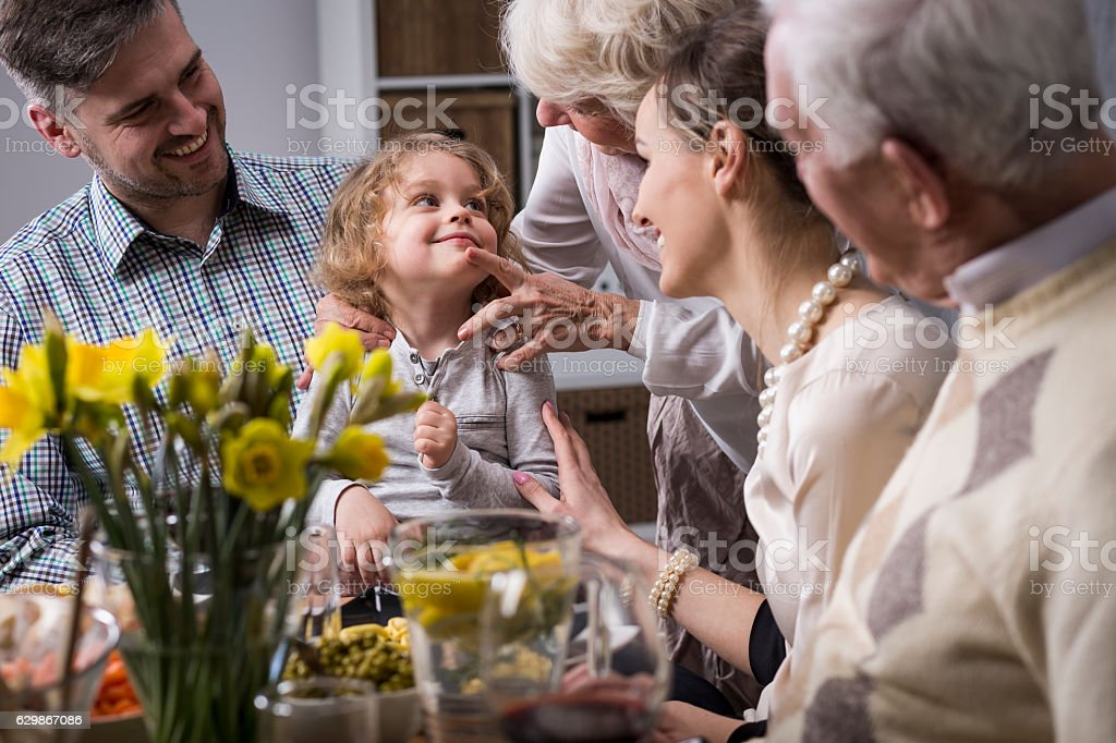 Three-generation family enjoying dinner stock photo
