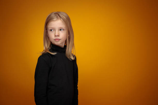 three-quarter portrait of pensive little blond girl in black stock photo