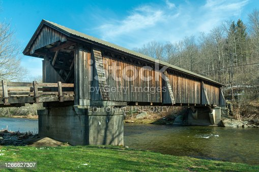 Livingston Manor, NY / United States - April 19, 2020: A three-quarter view of the Livingston Manor Covered Bridge spanning the scenic Willowemoc Creek