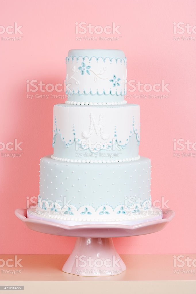 Three-tiered Cake Against Pink Background stock photo