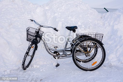 Three-wheeled bicycle in winter on a background of snowy hills, snowdrifts, fences and asphalt.