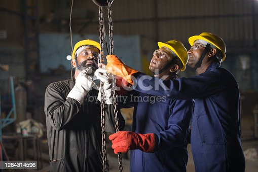 1047558948 istock photo Threeworkers operating chain hoist at factory 1264314596