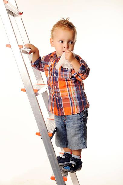 Trois ans garçon dans un t-shirt et un short à carreaux sur les escaliers. - Photo