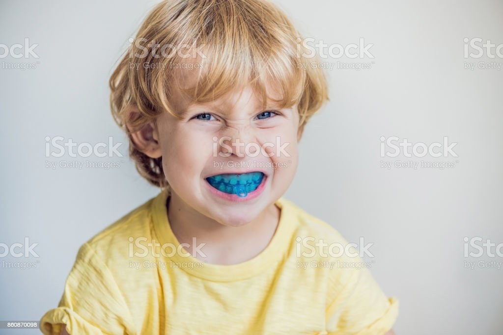 Three-year old boy shows myofunctional trainer to illuminate mouth breathing habit. Helps equalize the growing teeth and correct bite. Corrects the position of the tongue Three-year old boy shows myofunctional trainer to illuminate mouth breathing habit. Helps equalize the growing teeth and correct bite. Corrects the position of the tongue. Child Stock Photo