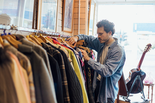 Man looking through clothing while at a thrift store.