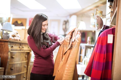 A beautiful young adult woman in her early 20's shops at a second hand thrift shop, searching through racks of clothes for cheap finds and treasures.  She examines a cool vintage leather jacket she's found.  Horizontal with copy space.
