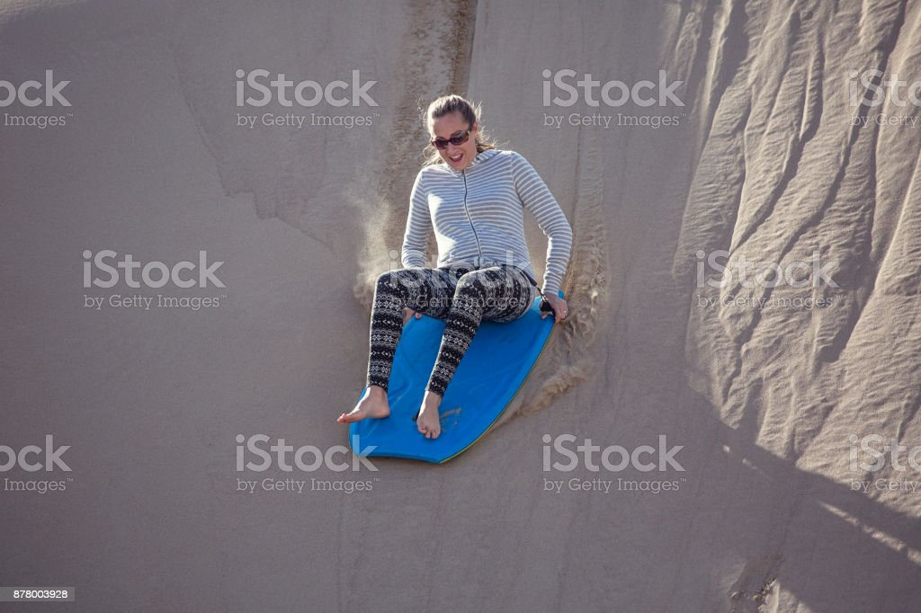 Thrill seeking woman Playing in the Sand Dunes Outdoor Lifestyle stock photo