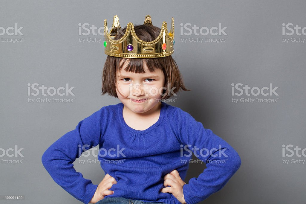 thrilled preschooler with confident attitude smiling with mollycoddled kid crown stock photo
