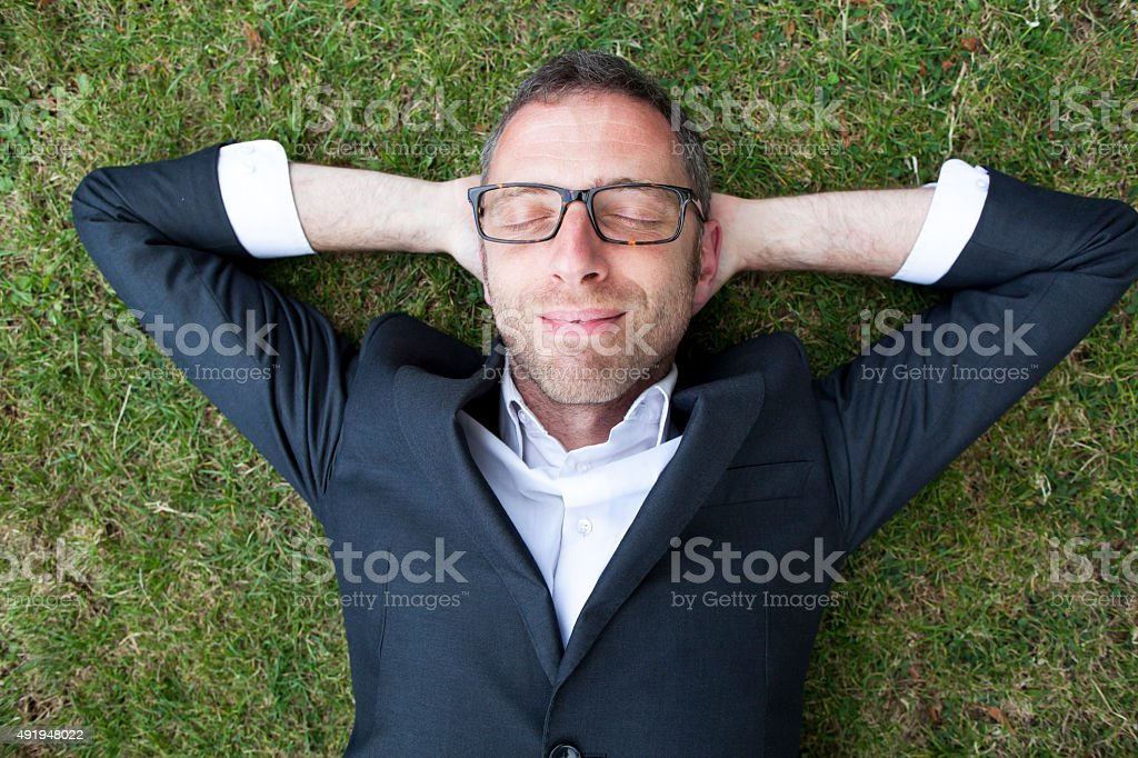 Thrilled relaxed businessman lying on grass outdoors stock photo