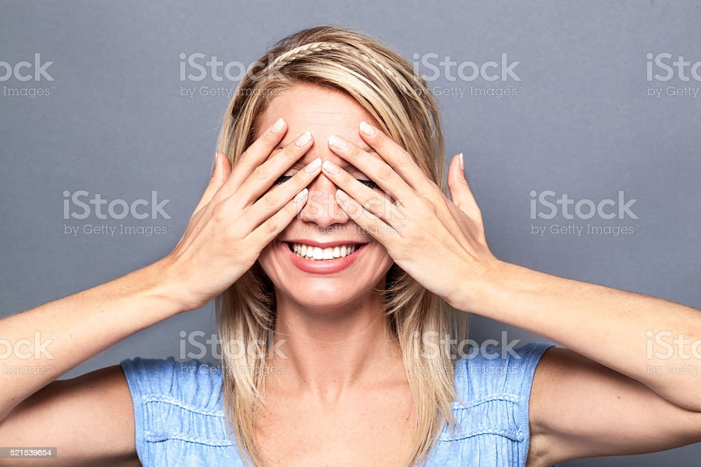 thrilled young blond woman hiding eyes for surprise and wellbeing stock photo