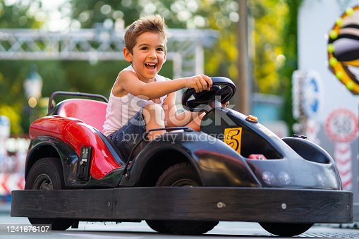 happy smiling 5 years old boy driving with go cart outdoors in summer, shallow focus background blurred