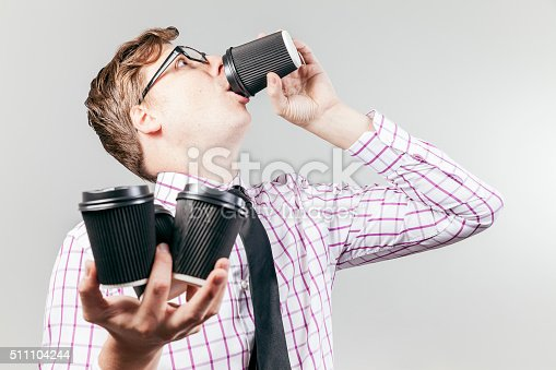 A business nerd drinks coffee out of a take away coffee cup, with 3 more in the other hand.