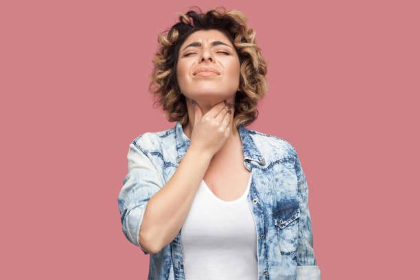 喉の痛みや寒さ。カジュアルな青いシャツに巻き毛の髪型を持つ若い女性の肖像画が立ち、彼女の痛みを伴う首を保持しています。 ストックフォト