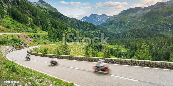 A group of motorcyclists travels on the Susten Pass mountain road through the Alps in summer.