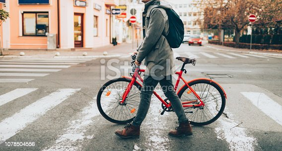 Young man walking through the city and pushing his bicycle