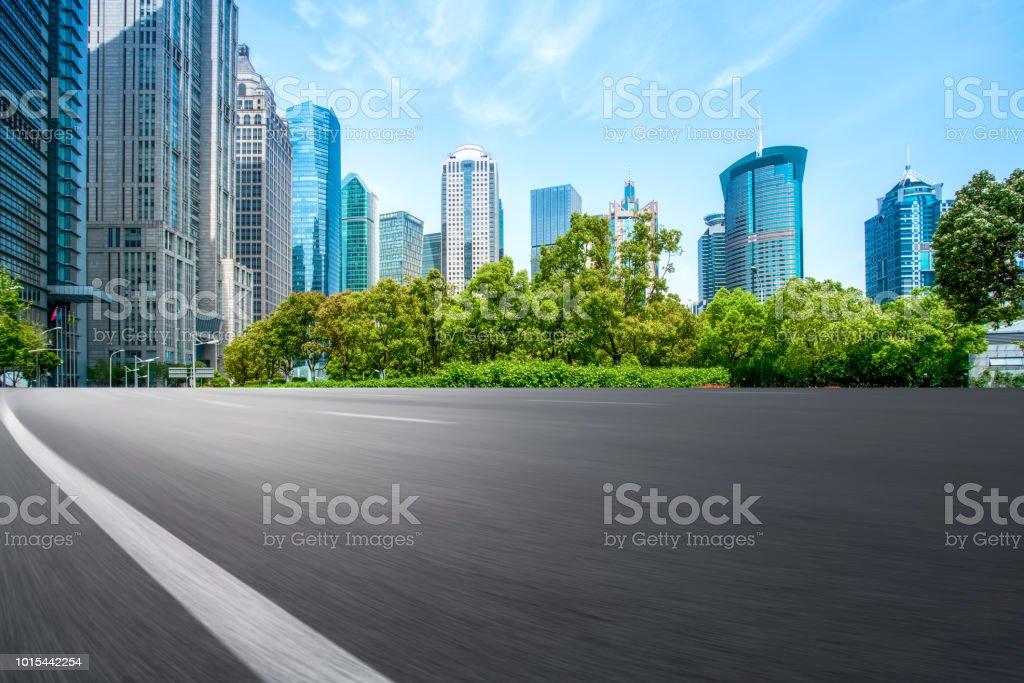 Through the empty asphalt road of modern city in Shanghai, China,