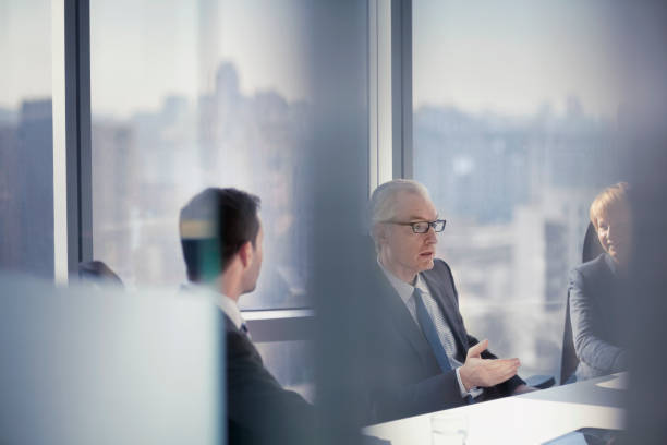 Through the glass view of businessman talking to colleagues in conference room meeting stock photo