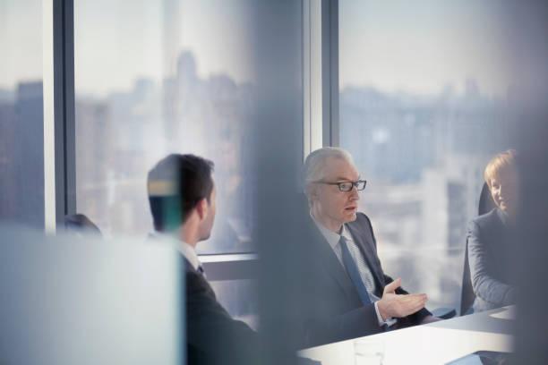Durch den gläsernen Blick des Geschäftsmannes im Gespräch mit Kollegen in Konferenzzimmertreffen – Foto