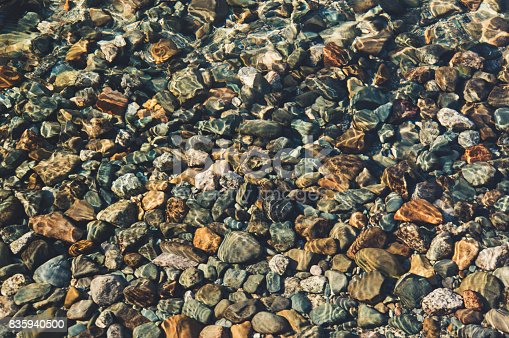 Through the thickness of the transparent water you can see the bottom consisting of pebbles, stones, sand. Background of a round stone pebbles on the bottom of the lake under water