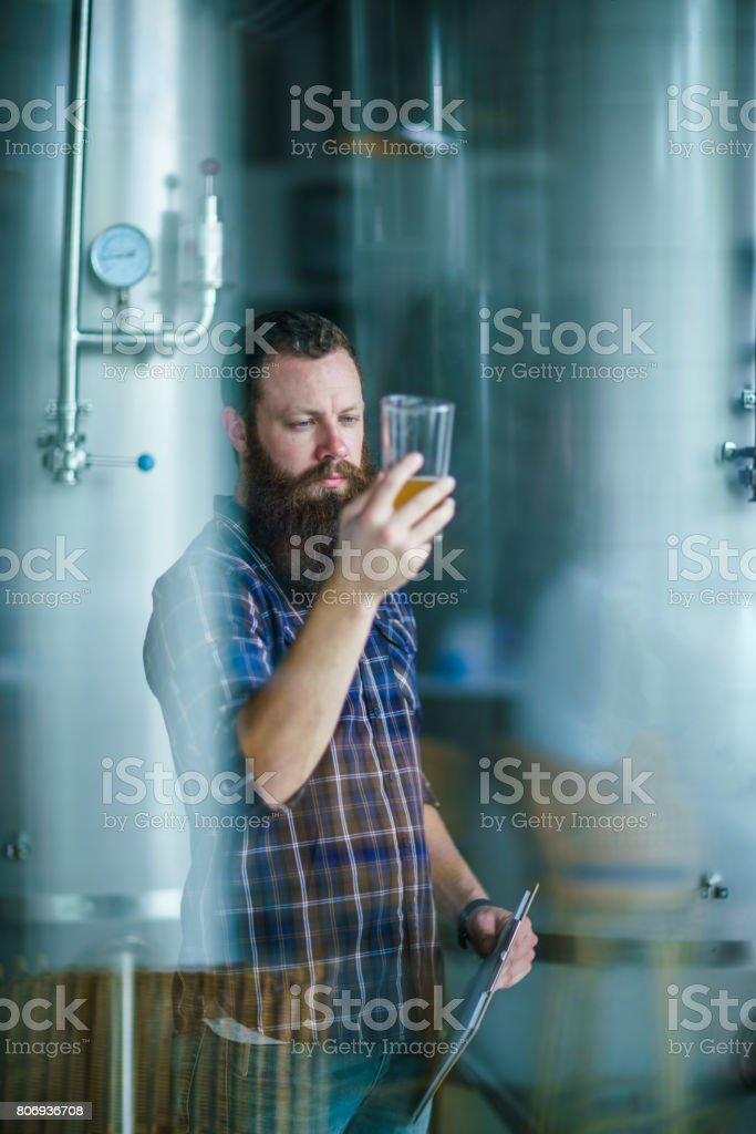 Through the window: master works in the brewery: beer testing, making remarks, quality control stock photo