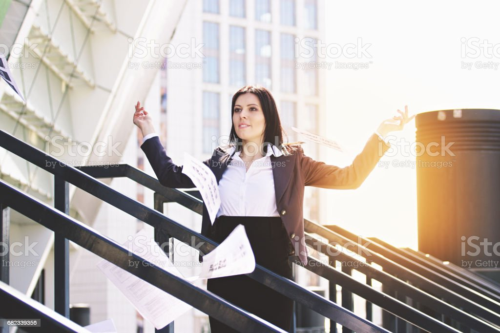 Throw it away. Portrait of beautiful business woman in smart casual clothes throwing paper documents away while standing near office building. foto stock royalty-free