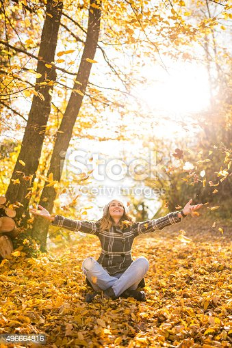 Young girl throwing leaves in the air on autumn day