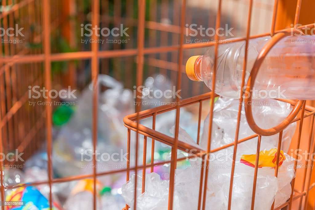 Throwing a bottle into trash bin for plastic products stock photo