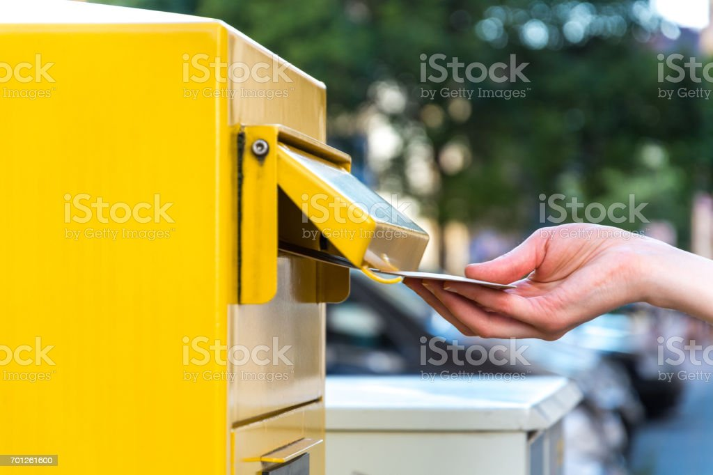 Throwing a letter in a german yellow mailbox stock photo