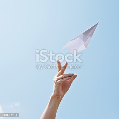 istock Throwing a paper airplane on sky 803062196