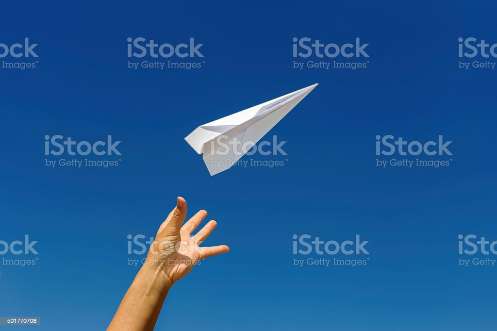 Throwing a paper airplane. stock photo