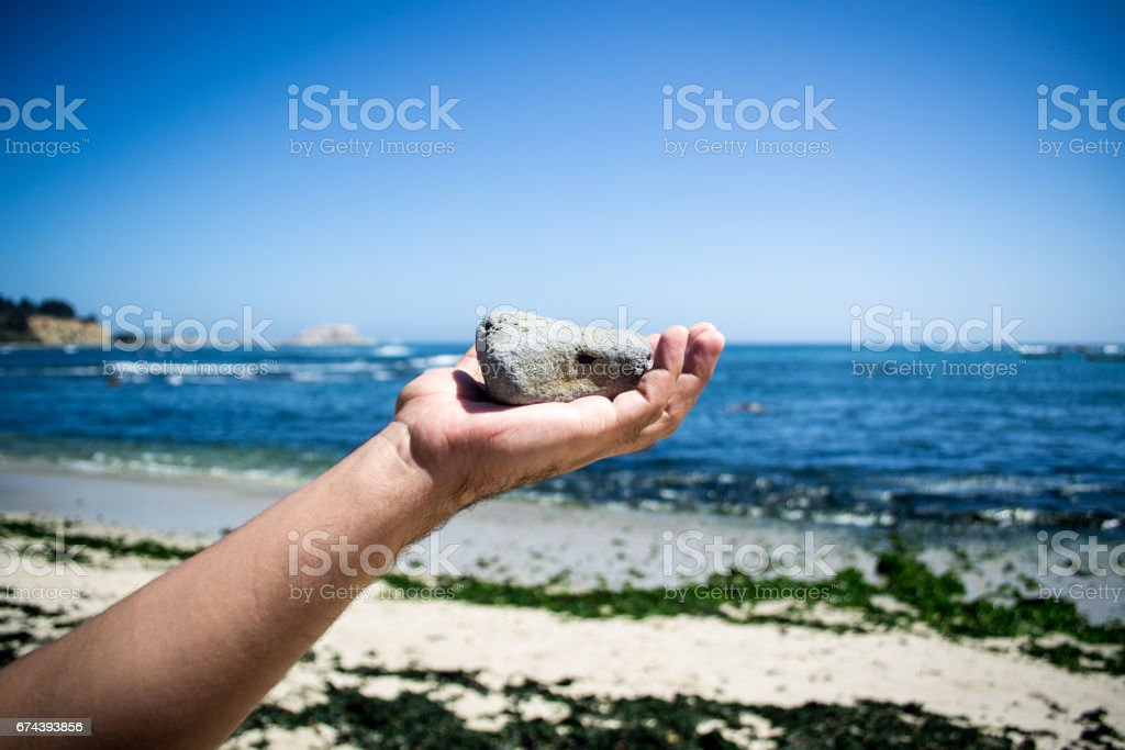 Throwing a stone. Beach background stock photo