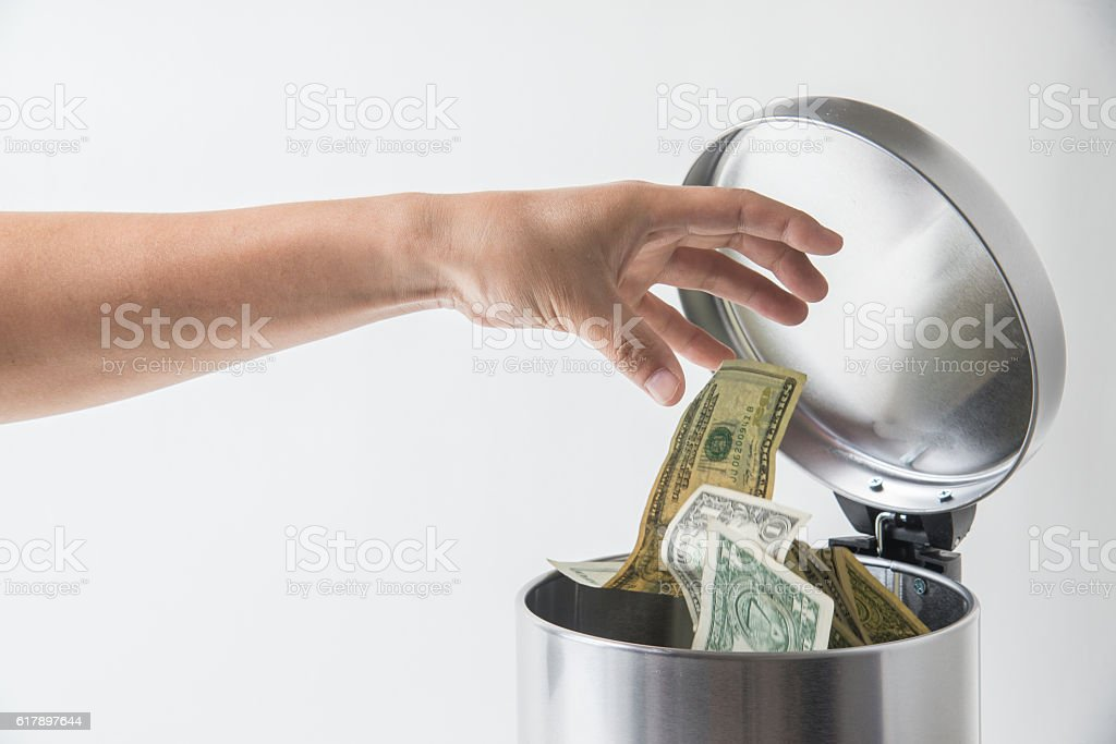 throwing away dollar in trashcan stock photo