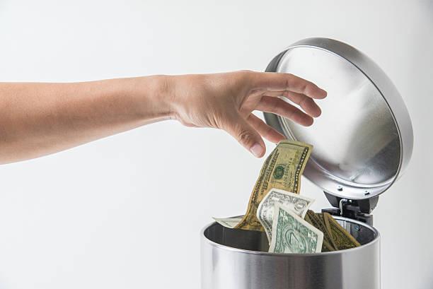 throwing away dollar in trashcan - jetée photos et images de collection