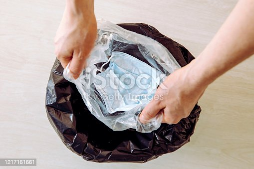 Throwing away single use medical  face mask. Packing it in one time plastic bag before throwing it in trash to prevent virus from spreading from mask to trash can and to people.