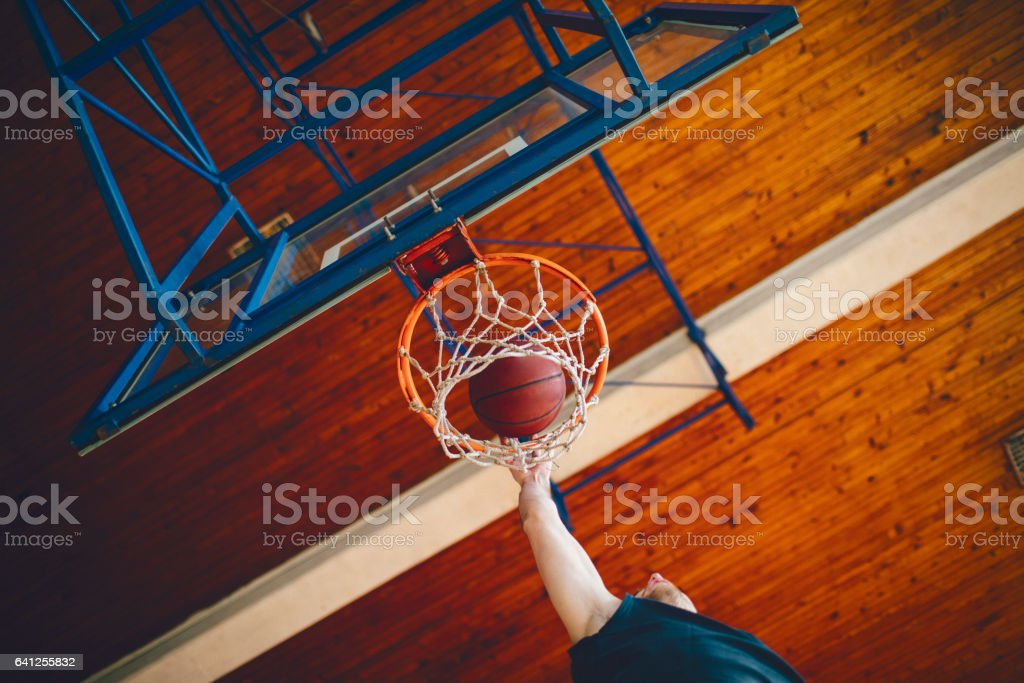 Playing basketball indoors. Player throwing ball in net