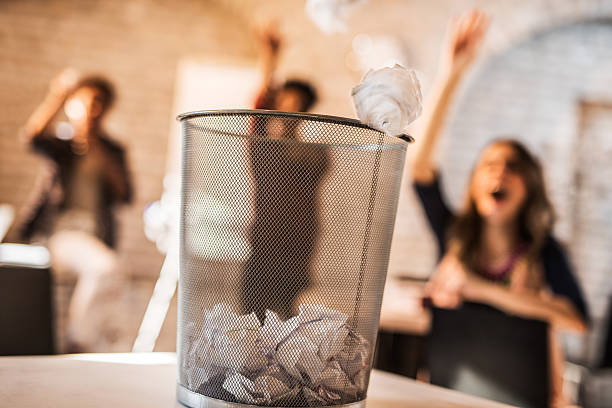 Throwing crumpled paper into a wastepaper basket. Group of people from the background tossing crumpled paper into a garbage can. throwing stock pictures, royalty-free photos & images