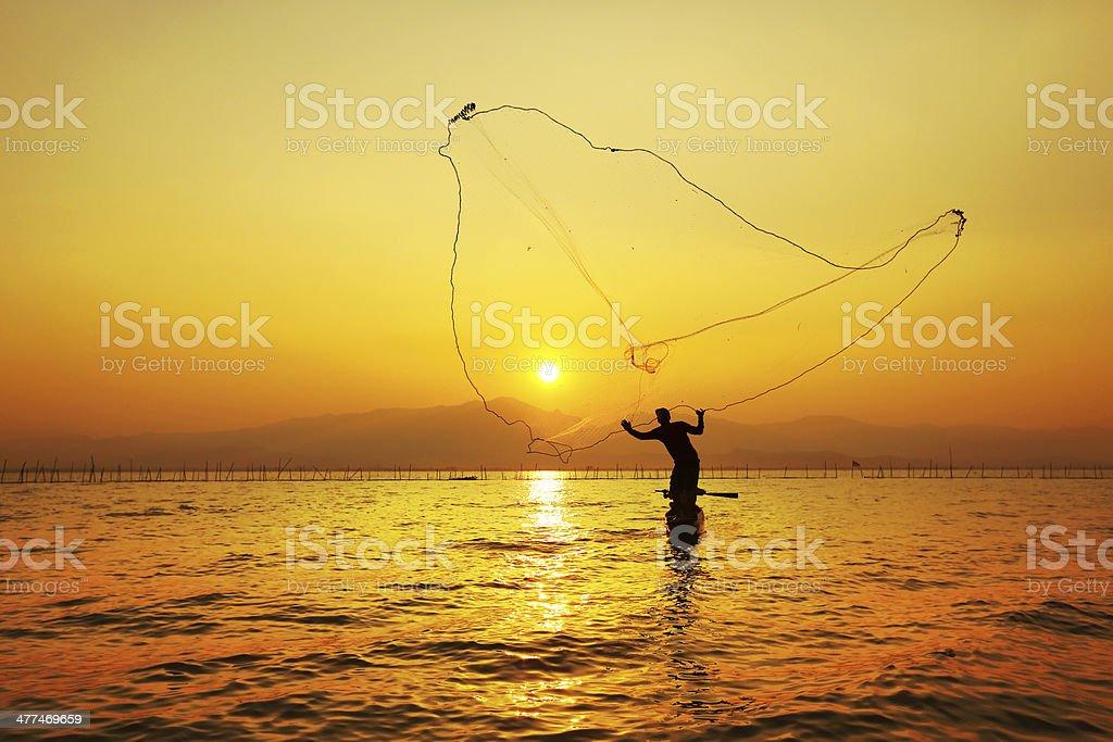 throwing fishing net during sunset , thai stock photo