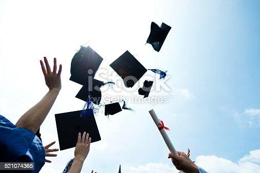 959532468 istock photo throwing graduation hats 521074365
