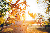 Young woman throwing dry autumn leaves in the air