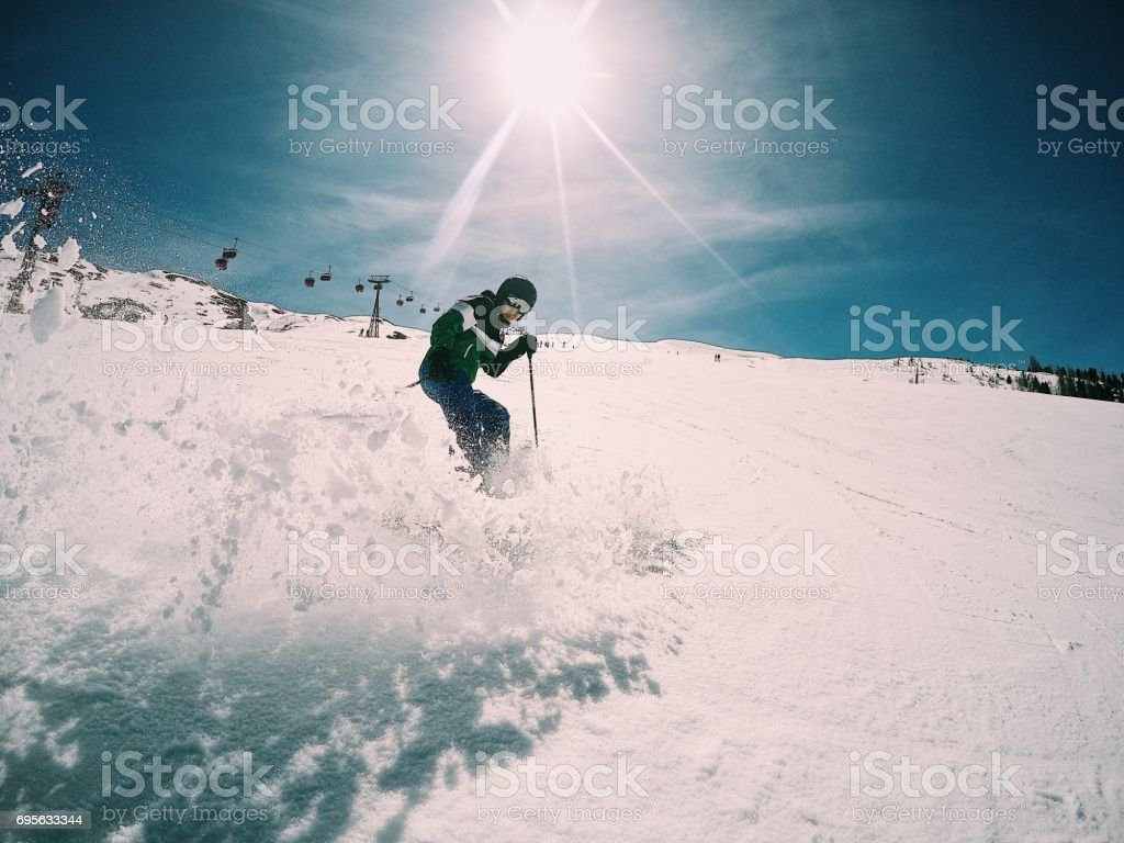 Skiing in an area full of snow on a sunny day.